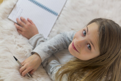 Portrait of smiling girl lying on the floor with pencil and booklet - SARF03476
