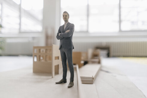 Miniature businessman figurine standing at architectural model - FLAF00116