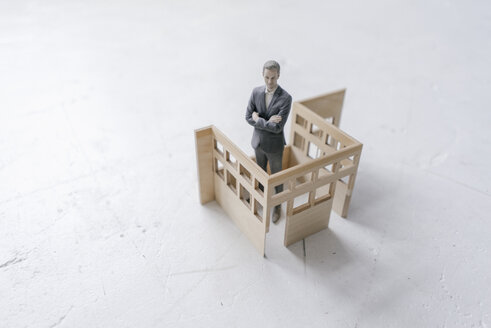 Miniature businessman figurine standing in architectural model - FLAF00119