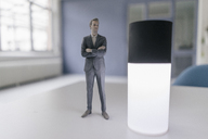 Miniature businessman figurine standing next to smart home device - FLAF00122