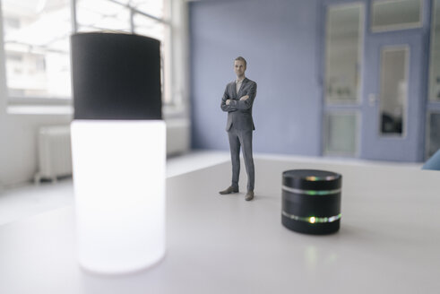 Miniature businessman figurine standing next to smart home devices - FLAF00125