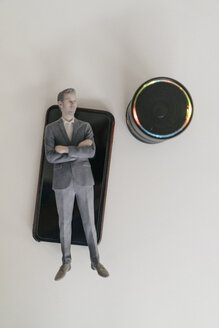 Miniature businessman figurine lying on smartphone next to smart home loudspeaker - FLAF00128
