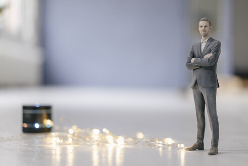 Miniature businessman figurine standing next to smart home loudspeaker with chain of lights - FLAF00131