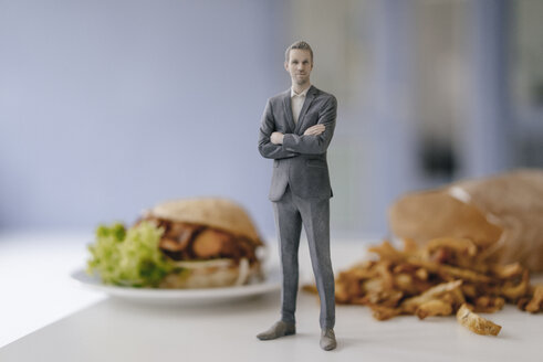 Miniature businessman figurine standing next to fast food - FLAF00137