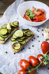 Bruschetta and various ingredients, bread with zucchini, tomato with basil in bowl - GIOF03787