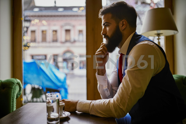 Pensive fashionable young man sitting in a cafe - ZEDF01099