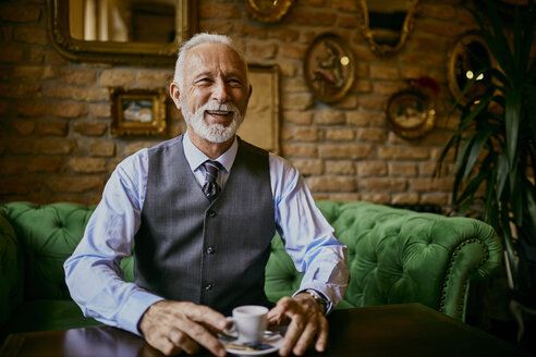 Portrait of elegant senior man sitting on couch in a cafe smiling - ZEDF01105