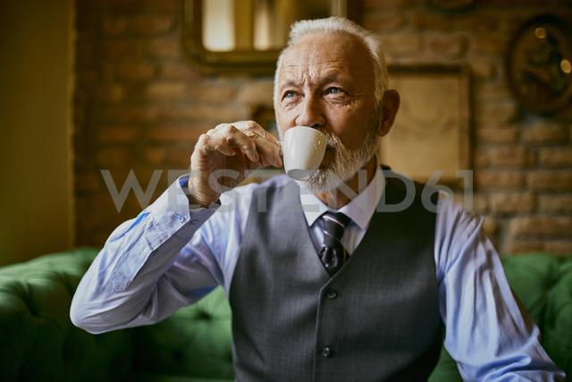 Elegant senior man drinking coffee in a cafe - ZEDF01108