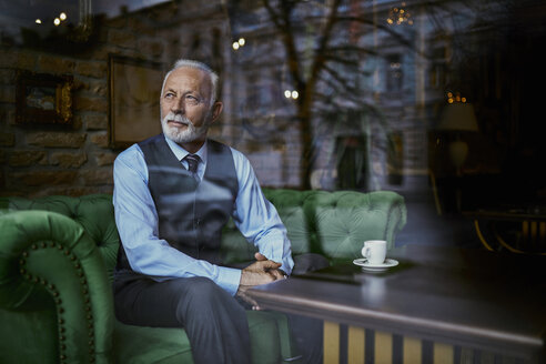 Elegant senior man sitting on couch in a cafe looking out of window - ZEDF01111