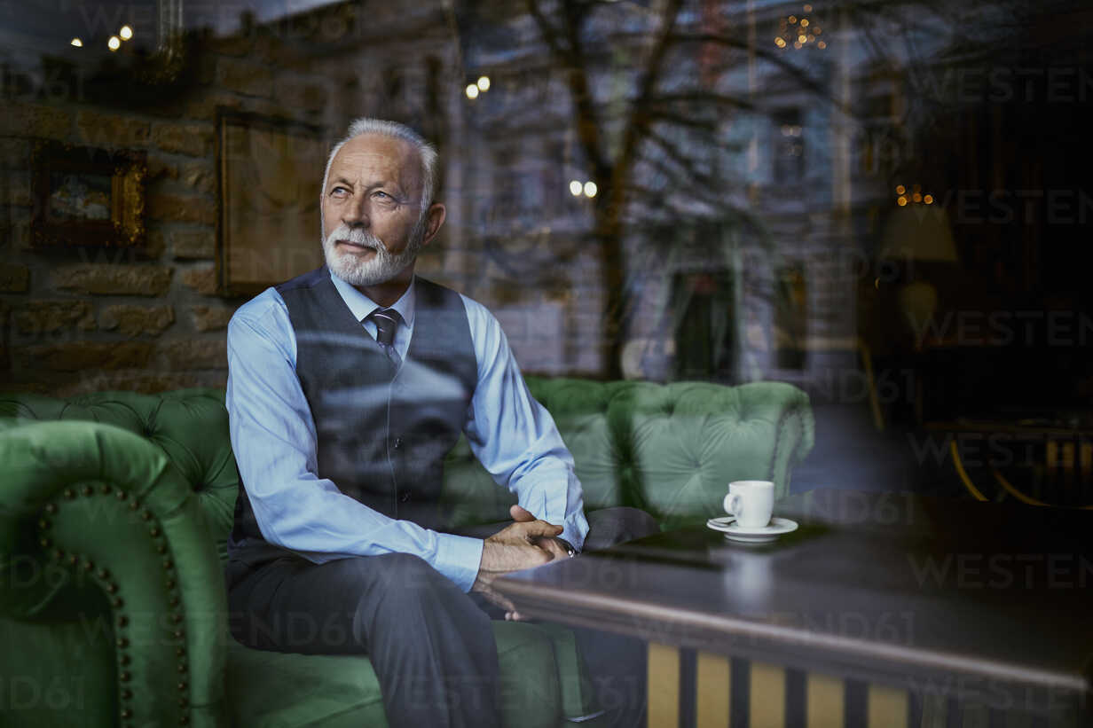 Elegant senior man sitting on couch in a cafe looking out of window - ZEDF01111 - Zeljko Dangubic/Westend61