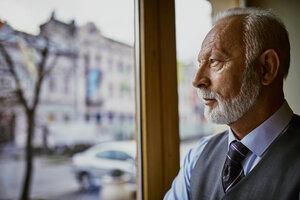 Elegant senior man looking out of window - ZEDF01114