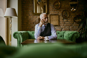 Elegant senior man sitting on couch in a cafe on cell phone - ZEDF01117