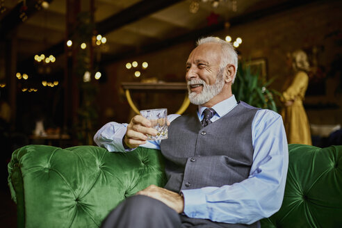 Portrait of elegant senior man sitting on couch in a bar holding tumbler - ZEDF01120
