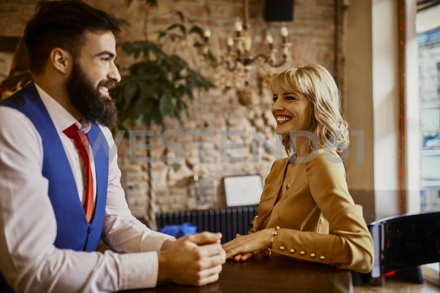 Elegant couple smiling at each other in a bar - ZEDF01123