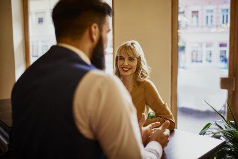 Elegant woman smiling at man in a bar - ZEDF01126
