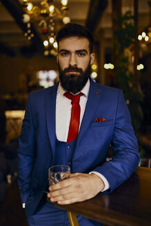 Portrait of elegant young man in a bar holding tumbler - ZEDF01135