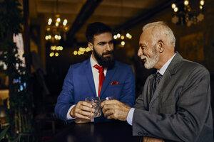 Two elegant men in a bar clinking tumblers - ZEDF01144