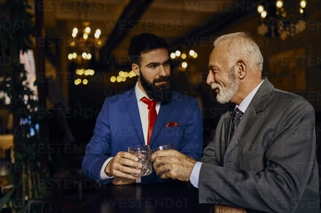 Two elegant men in a bar clinking tumblers - ZEDF01144 - Zeljko Dangubic/Westend61