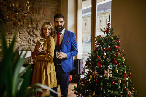 Portrait of elegant couple with drinks at Christmas tree - ZEDF01150