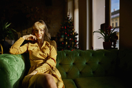 Portrait of smiling elegant woman sitting on a couch with Christmas tree in background - ZEDF01153