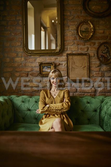 Portrait of smiling elegant woman sitting on a couch - ZEDF01156