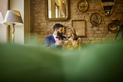 Elegant couple with drinks sitting on couch embracing - ZEDF01162