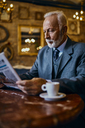 Elegant senior man reading newspaper in a cafe - ZEDF01177