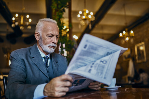 Elegant senior man reading newspaper in a cafe - ZEDF01180
