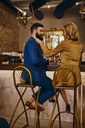 Elegant couple sitting at the counter in a bar - ZEDF01183