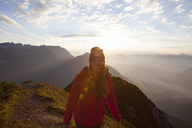 Austria, Tyrol, portrait of smiling hiker above Achensee at sunrise - FAF00081