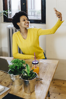 Young woman sitting at table, taking a selfie - GIOF03802
