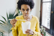 Young woman eating Asian noodles for lunch with chopsticks - GIOF03820