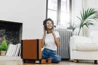Young woman sitting on grounf listening music from record player, using headphones - GIOF03823