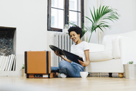 Young woman sitting on grounf listening music from record player - GIOF03835