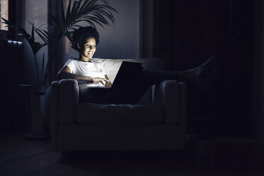 Young woman watching online tv at night, using laptop - GIOF03847