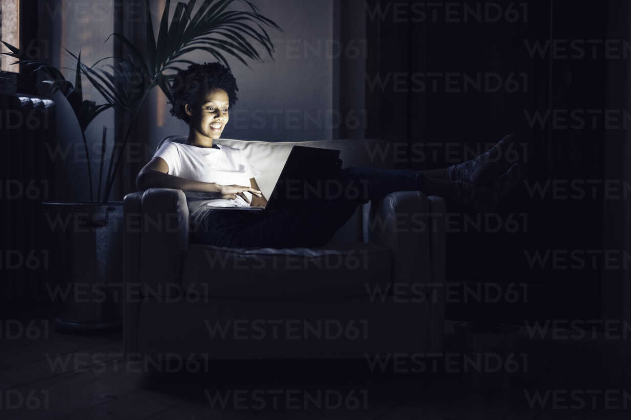 Young woman watching online tv at night, using laptop - GIOF03847 - Giorgio Fochesato/Westend61