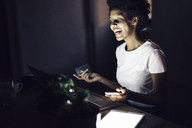 Young woman with credit card, shopping online at night from home - GIOF03853