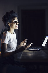 Young woman with credit card, shopping online at night from home - GIOF03856