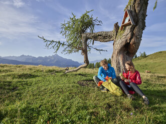 Austria, Tyrol, Mieming Plateau, hikers having a break on alpine meadow - CVF00054