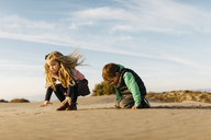 Two children playing with the sand on the beach in winter - JRFF01528