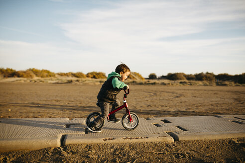 Boy running with a bike on the beach in winter - JRFF01531
