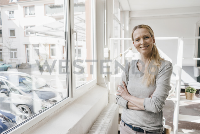 Portrait of smiling woman standing at the window - KNSF03551 - Kniel Synnatzschke/Westend61