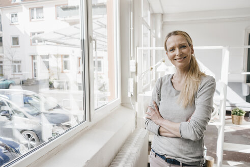 Portrait of smiling woman standing at the window - KNSF03551