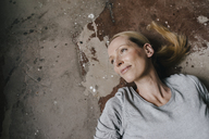 Portrait of smiling woman lying on the floor - KNSF03557