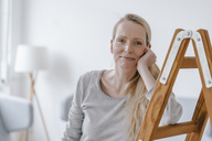 Portrait of blond woman leaning on a ladder - KNSF03569