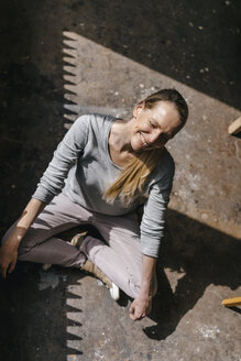 Smiling woman sitting on the floor with closed eyes - KNSF03578