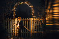 Boy putting up Christmas lights at garden fence - NMS00189