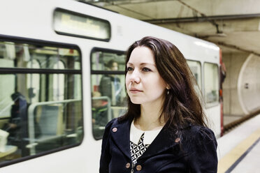 Germany, Cologne, portrait of young woman waiting at underground station platform - JATF00999