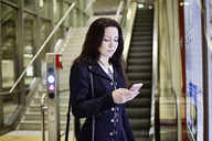Portrait of young woman looking at cell phone in underground station - JATF01008