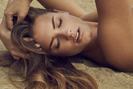 Portrait of lascivious young woman lying on the beach - PNEF00393